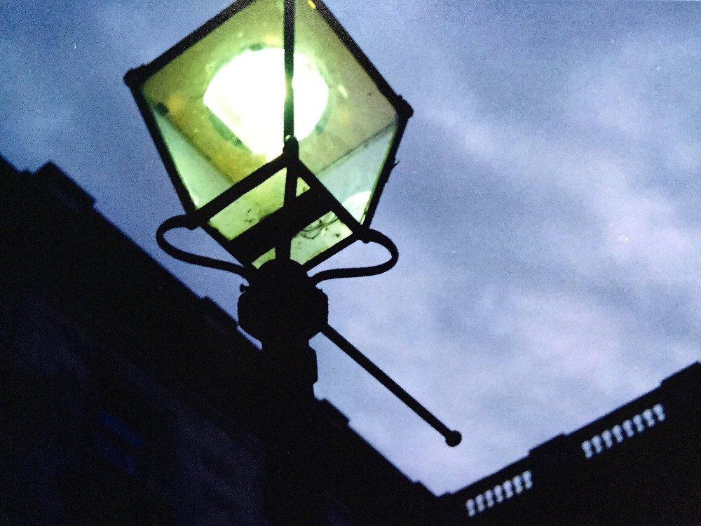 Picture of a old-looking square lampost shining against a shadowy building and a dark blue sky. The light it emits looks green.