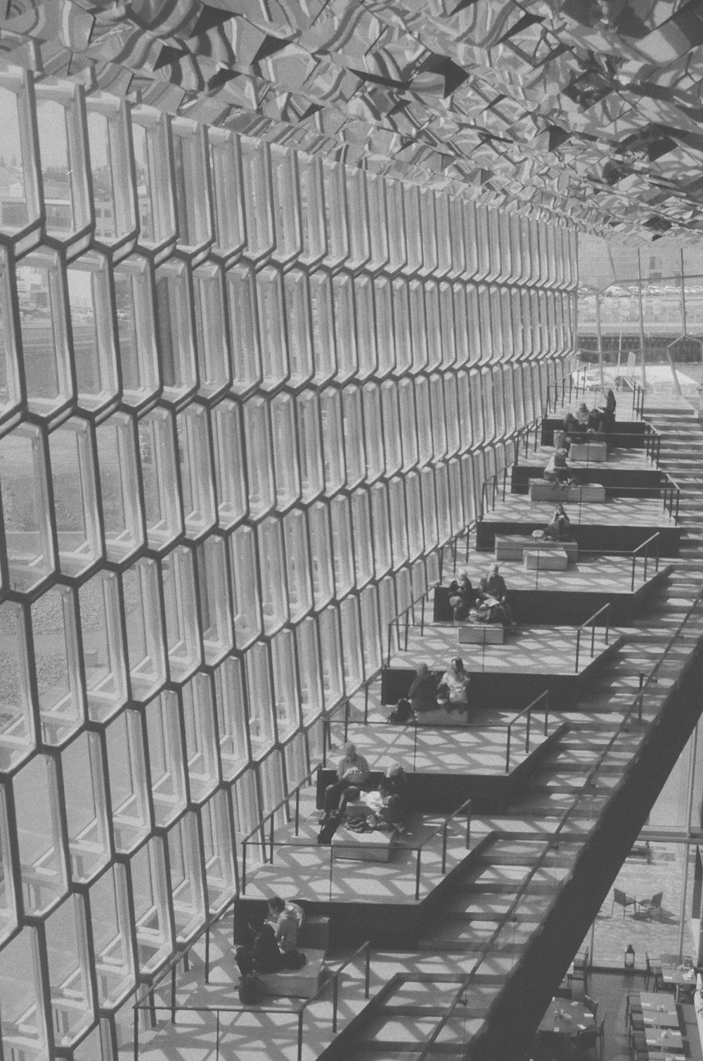 The inside of a building. Steps lead to a series of uncovered resting spaces, which are also set up in the form of steps. They are illuminated by the light coming in through a wall made entirely of glass sections that look reminiscent of a honeycomb. The photograph is in grayscale.