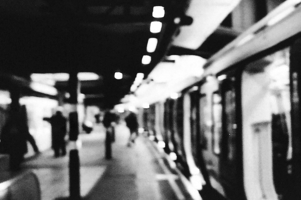 A blury picture in black and white of the London tube.