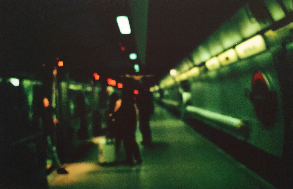 Blurry picture of the London tube in green and black tones.