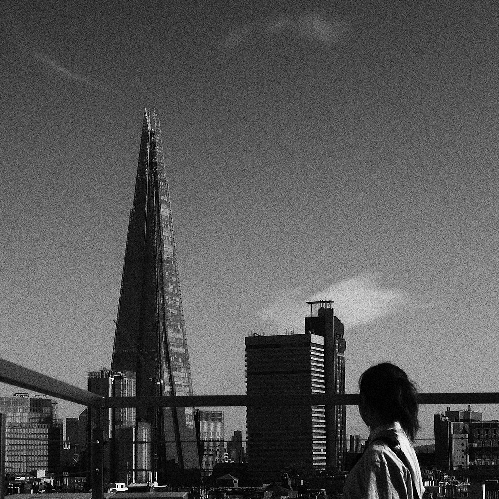 A woman on the right of a rooftop looking at The Shard. The picture is a grainy black and white.