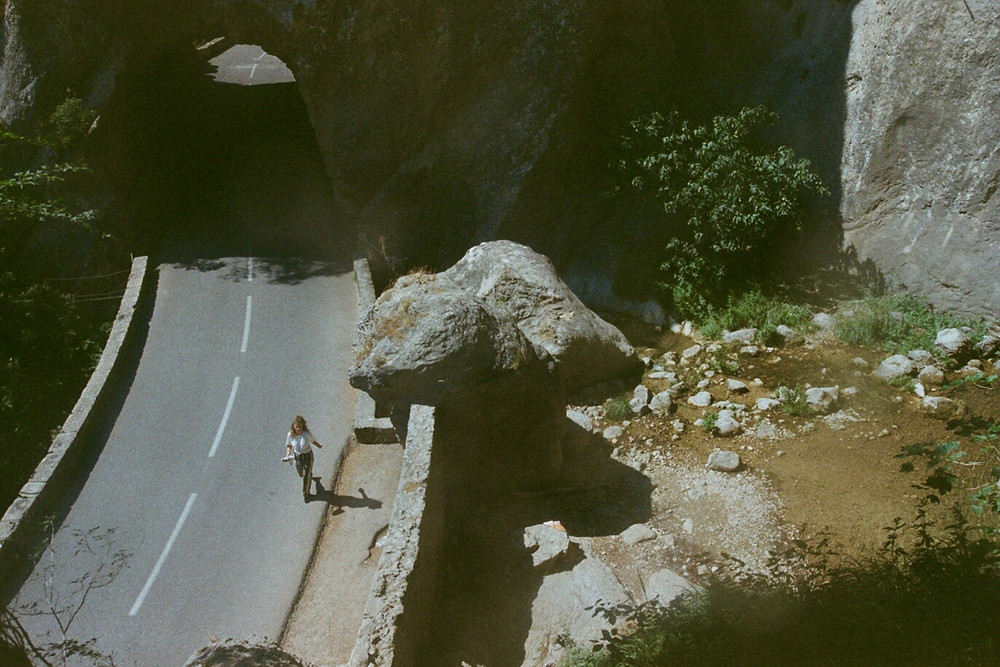 An areal shot of a woman walking along an empty road in the middle of what looks like a remote, mountainy forest. A large rock seems to be lodge onto the side of the road, and is looming above the walking girl.