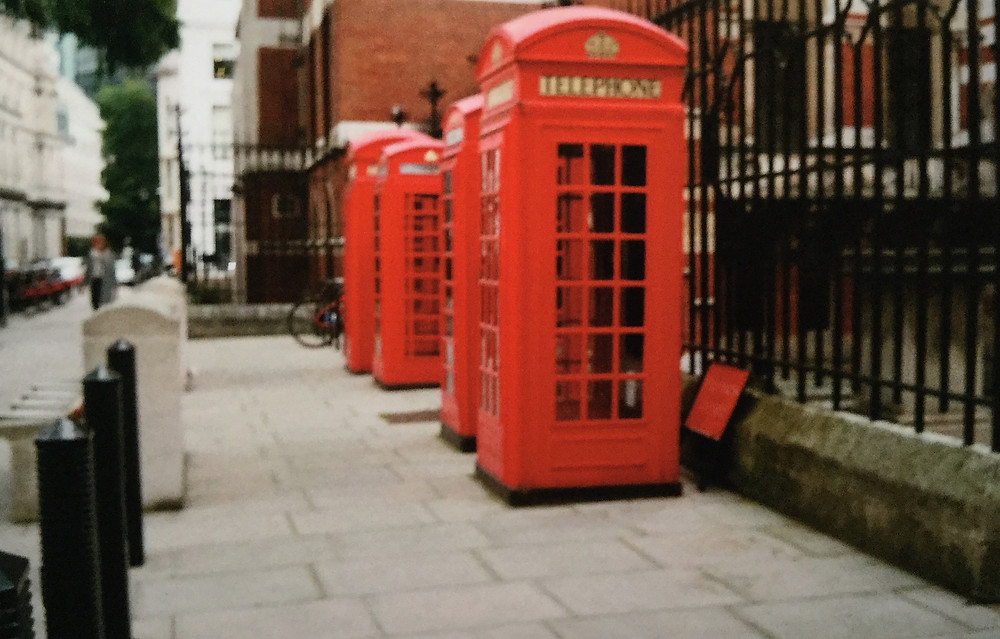 A blurry picture of some red telephone boxes.