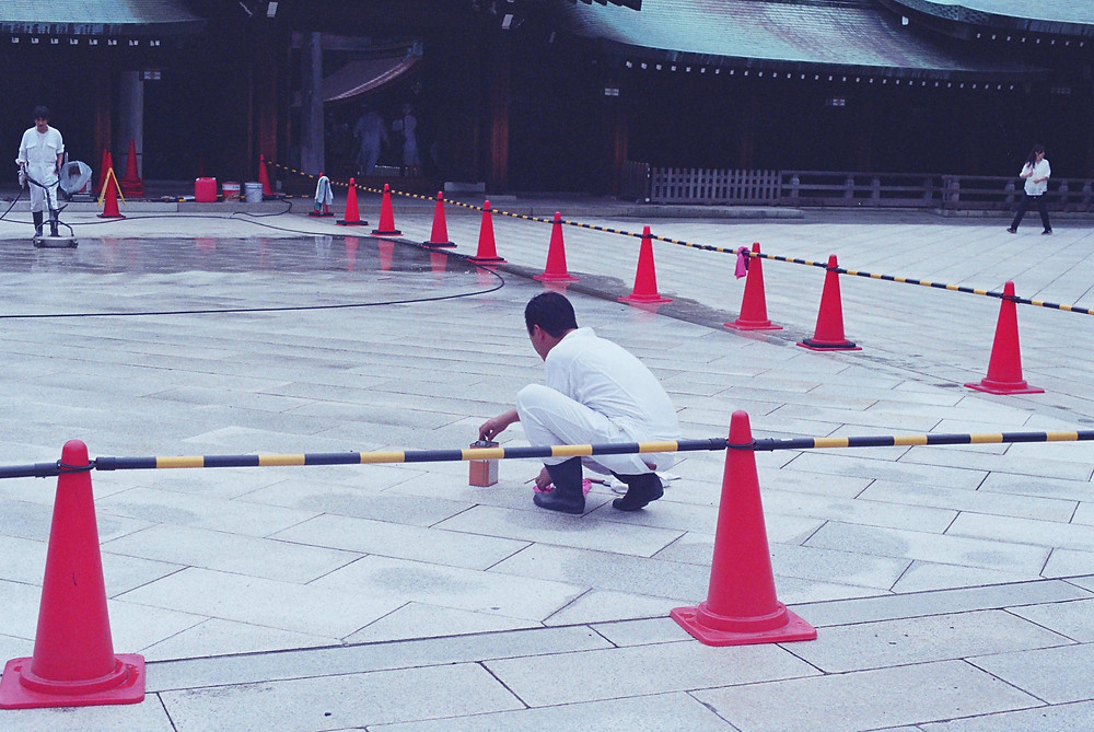 A cleaning operation at a Japanese temple. In the foreground, a Japanese man crouches on the ground with a small box in one hand and a piece of red cloth on the other. He is wearing a white jumpsuit and black boots. Further in the background, another Japanese man in the same uniform as the first cleans and polishes the wet floor using a machine. Both of these men are enclosed by red cones connected by black-and-yellow bars. In the background, to the right and outside the perimetre marked by the cones, a woman in a white shirt and black pants is walking.