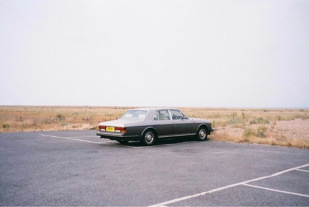 A solitary gray car in a parking lot. Past the paved area where the car rests, there is nothing but an endless stretch of yellowish, dried-up grass. The sky is a light gray.