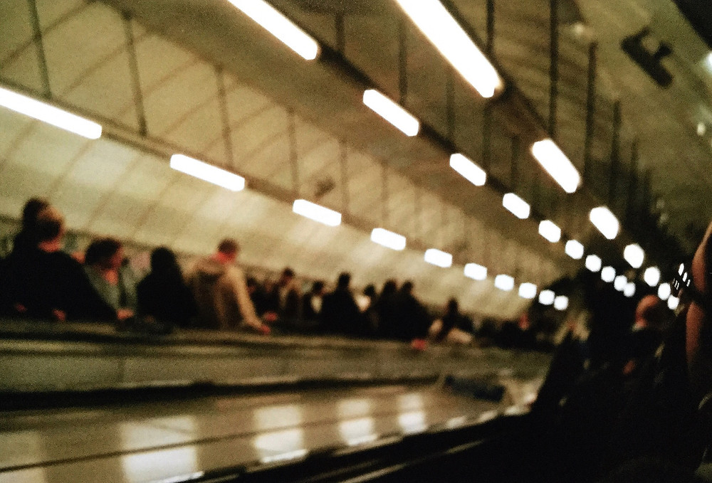 Blurry picture of the London tube escalators in a creamy white hue.