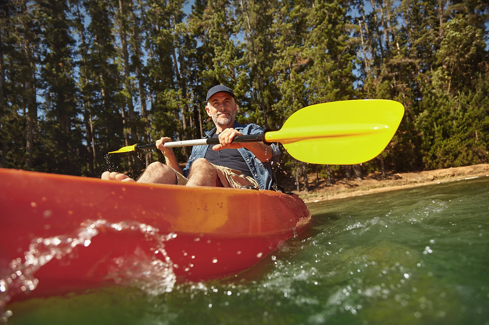 mature-man-canoeing-on-summer-day-PUJGUD