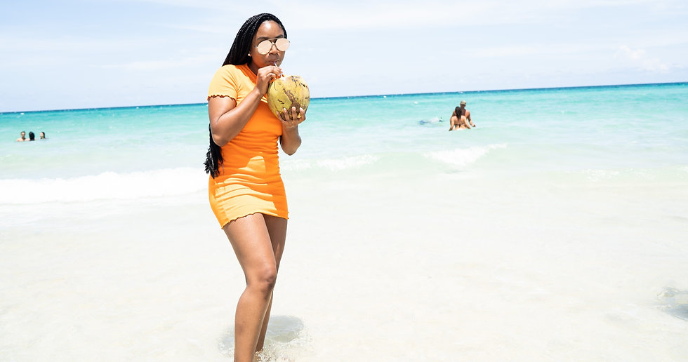 Black woman drinkin out of a coconut in cuba while wearing an orange dress on a beach with crystal clear beach water