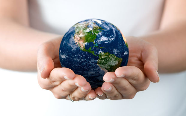 Two hands folded holding a colorful blue globe of the world.