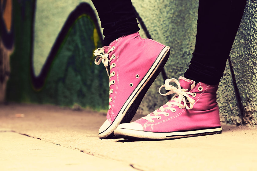 Close up of pink sneakers worn by a teen