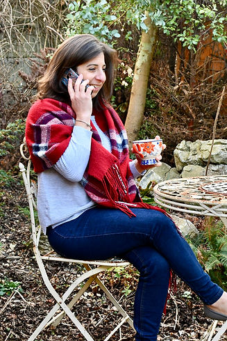 Talia seating outside talking to a client on the phone