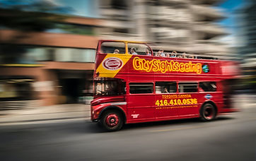 A red city sightseeing bus in focus, around it is blurred like the world is moving really fast around it.