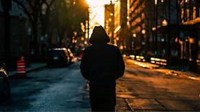 A hooded man in the suburbs facing a sunset