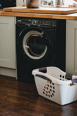 White plastic laundry basket beside a black front load washing machine.