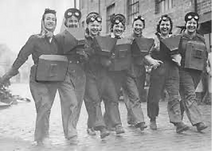 Black and white photo of seven ladies in uniforms with bags