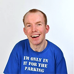 A caucasian male wearing a blue shirt smiling