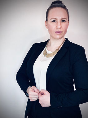 A brown haired woman wearing a suit posing with her arms at her waist