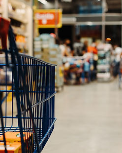 : A shopping trolley in forefront, in the background out of focus the isle of a supermarket
