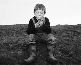 A black and white photo of a caucasian boy sitting on grass