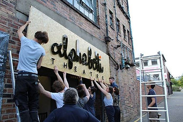 "A group of people lifting a big sign that says ""Alphabetti Theatre"""