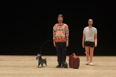 three figurines, a black schnauzer, a person with a suitcase and a hat, a person with shorts and a shirt