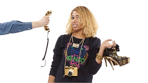 A blonde lady holding gold and black heels with a chordless phone being handed to her