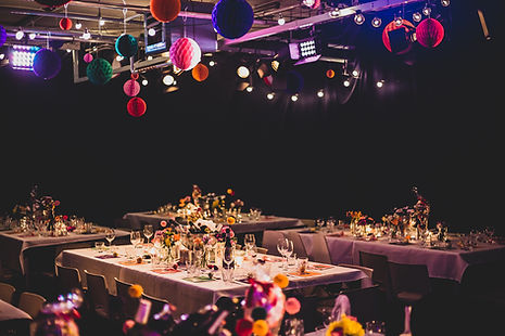 Four tables set for a celeberation. There are party decorations hanging from the ceiling
