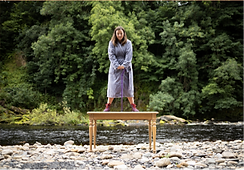 Woman standing on a table with a river and trees behind her