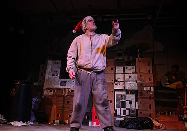 A caucasian male in a santa's hat and a scruffy brown sweatsuit. He's on a theatre stage