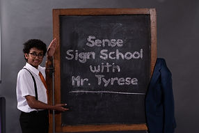 A small person with glasses dressed as a professor standing beside a big blackboard