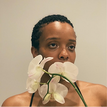 A short haired person with white flowers covering their mouth