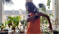 A lady in a dance pose by a window with house plants behind her