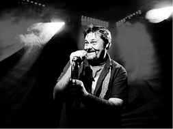 Black and white image of a man on a stage with a microphone