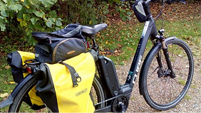 A black bicycle with yellow pannier bags