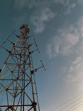 A black and grey phone tower underneath a deep blue sky