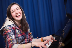 A caucasian lady with brown hair smiling and playing the piano