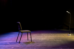 A chair and a microphone on a dark spot-lit stage