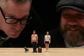 Two caucasian men staring at three small figurines. A black schnauzer and two men