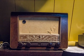 A brown and grey aged transistor radio in front of a mustard yellow wall