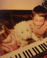 a sepia tone photo of two children and a white terrier