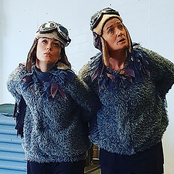Two white females in frilly grey jumpers and WW2 flying caps and goggles. The women are dressed as pigeons