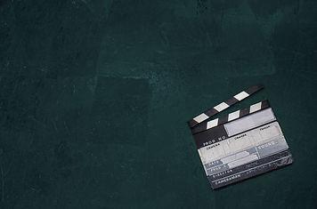 a clapperboard lies on a dark background