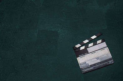 a clapperboard lies on a dark background