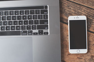 A laptop keyboard and a sleeping iphone on wooden desk.
