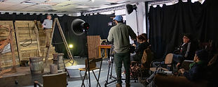 A lady on a set, standing on a ladder prop. She is being filmed by a camera-man and two crew members.