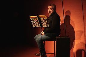 A man on a stage sitting reading from a book on a stand