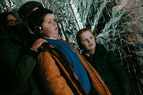 Two boys in the foreground, wearing headphones looking scared - behind them are their parents. They're in a room lined in shiny silver material