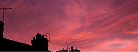 A pink sky with the silhouette of a chimney