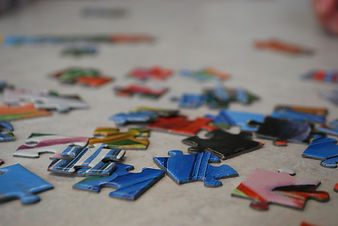 Scattered multicoloured puzzle pieces on the floor.