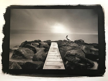 A long exposure shot of a pelican perched in rocks and a jetty printed in platinum palladium process
